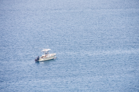 A small white fishing boat moored in the middle of deep blue bay photo