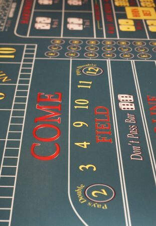 Come line and field numbers on a green felt craps table