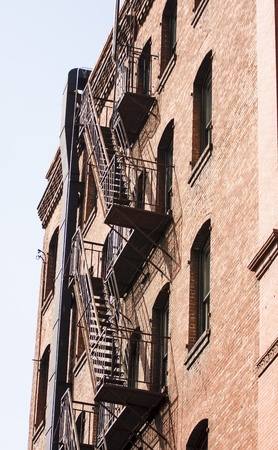 escape: Black iron fire escape on an old red brick building