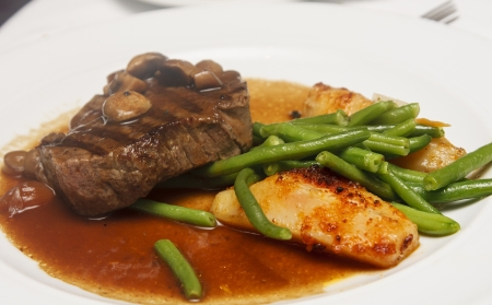 A steak with mushroom gravy on plate with green beans and potato