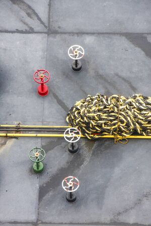 Yellow and black rope on the deck of a ship with red, green, and white valves Stok Fotoğraf