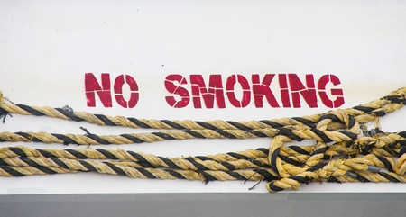 No Smoking in red paint on a white ships hull with yellow and black rope Imagens