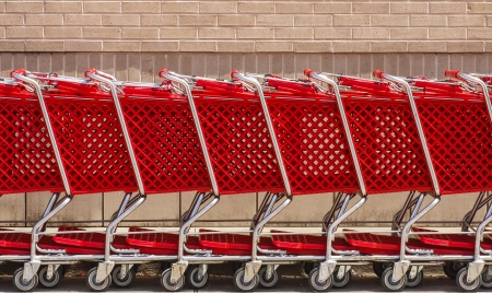 shopping buggy: Row of red shopping carts by brick wall