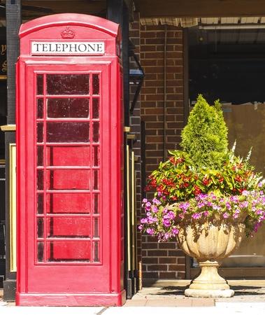 Une vieille cabine téléphonique rouge britannique sur un trottoir par une plante en pot Banque d'images - 14725437