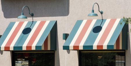 Green Vitange Lamps on Beige stucco wall over striped awnings Banque d'images