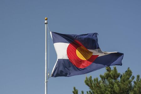 The state flag of Colorado blowing in a breeze under a blue sky