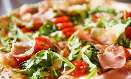 A fresh baked pizza on a cheese, arugula and tomato pizza