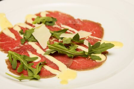 An appetizer of carpaccio garnished with fresh arugula, parmesan and sauce Imagens