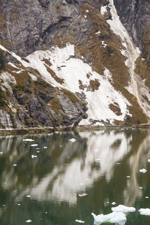 Snow on Rocky fjord by calm green water in Alaska