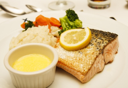 broiled: Broiled Atlantic salmon garnished with lemon slice with melted butter, rice, and fresh steamed vegetables