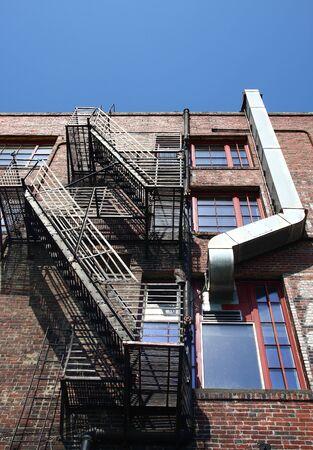 An old brick building with a black iron fire escape and metal ductwork