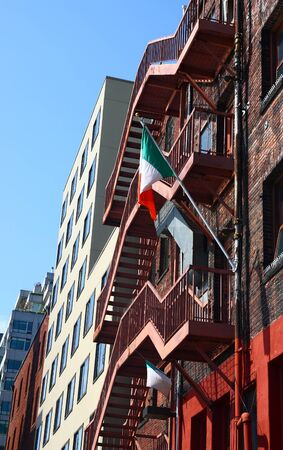 An Irish flag on a red rusty fire escape on a brick building Reklamní fotografie