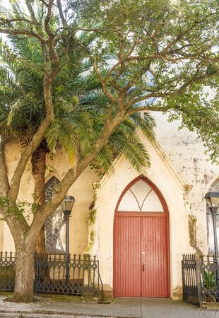 spirtual: An old brown plaster church with a red door Stock Photo