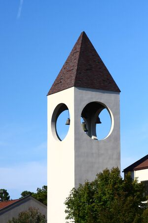 A churchs bell tower against a clear blue sky