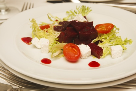 Fresh appetizer salad of lettuce, beets, goat cheese and cherry tomatoes Imagens
