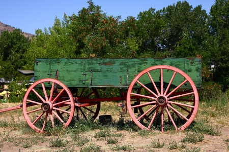 spoked: An old wood wagon with spoked wheels in park