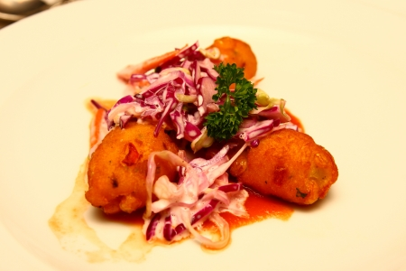 An appetizer of conch fritters with a cabbage slaw