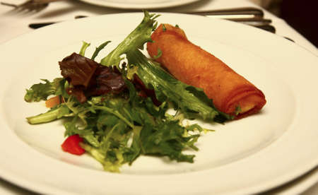 An appetizer of a spring roll and fresh salad of field greens photo