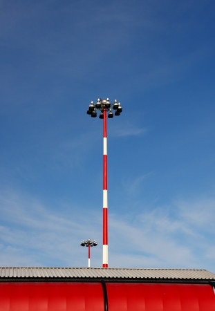 Red and white light poles by red metal building under blue skies 版權商用圖片