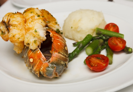 A lobster tail on plate with mashed potatoes, asparagus and grape tomatoes