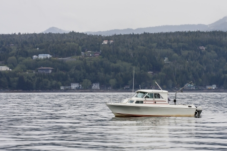 A white fishing boat cruising up a channel in Alaska photo