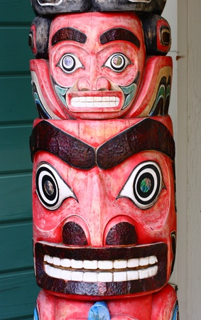canadian pacific: An old wooden carved totem pole in Alaska painted red Stock Photo