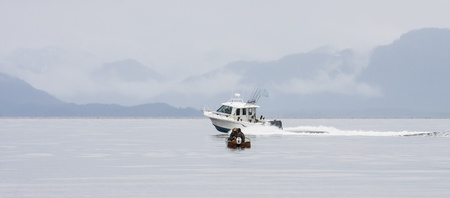 A small fishing boat with two fishermen being past and almost swamped by a large fishing boat speeding past photo