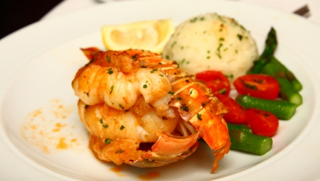 A lobster tail with butter sauce served with green beans, asparagus, grape tomatoes and mashed potatoes Stok Fotoğraf