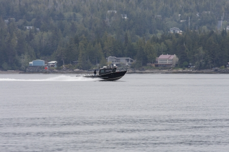 A black fishing boat speeding along shore near homes in Alaska photo