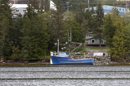 An old blue fishing trawler tied up on the shore of an Alaskan waterway photo