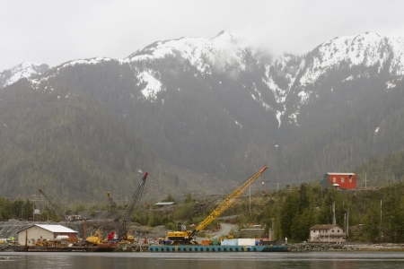 frontend: A red building above construction equipment on shore of Alaska