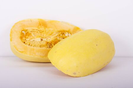 A large spaghetti squash cut in half with seeds and pulp