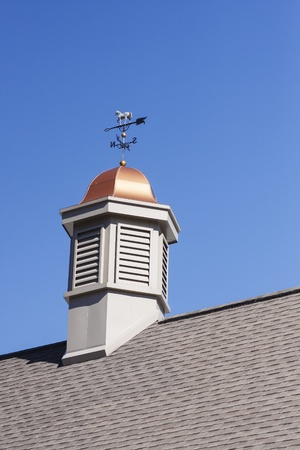 vents: A cupola with copper roof and weather vane on a roof under a clear blue sky