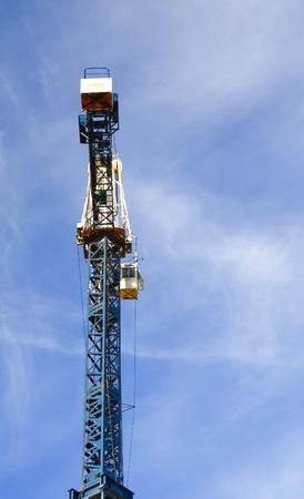 A blue construction crane against a blue sky Imagens