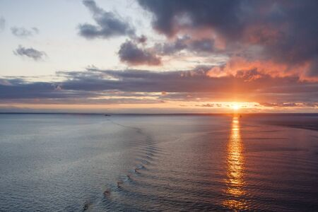 Sun coming over horizon with ships wake on calm water
