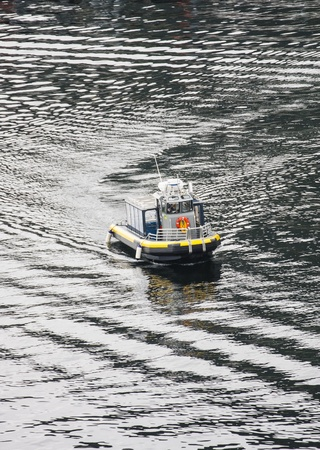 enclosed: A small enclosed tour boat rubber dinghy cruising across harbor Stock Photo