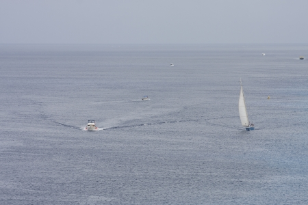 cutting through: Speedboat cutting through water near sailboat in blue sea Stock Photo