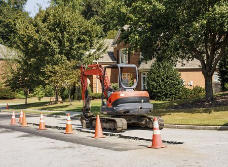 Orange construction equipment on a residential street doing repairs
