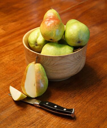 paring knife: Fresh bartlett pears in a wood bowl on a table with one cut by paring knife