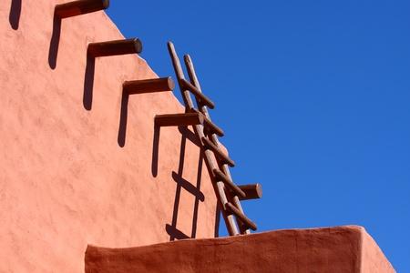 adobe wall: Una scala in legno vecchio appoggiato a un muro rosso adobe sotto un cielo blu