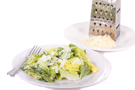 A fresh caesar salad with shaved parmesan cheese and a grater on white plates