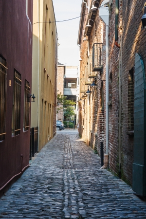An alley between old brick buildings paved with cobblestones Stok Fotoğraf