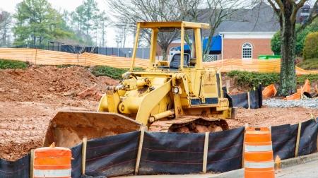 silt: Large, heavy construction equipment on a fresh, dirt site behind silt fence