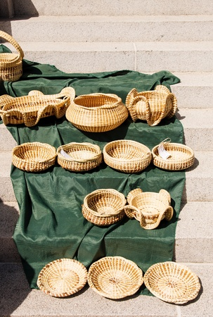Hand woven baskets in a market on green blanket on steps Stok Fotoğraf