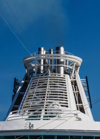superstructure: White superstructure and smokestack on a cruise ship against a blue sky