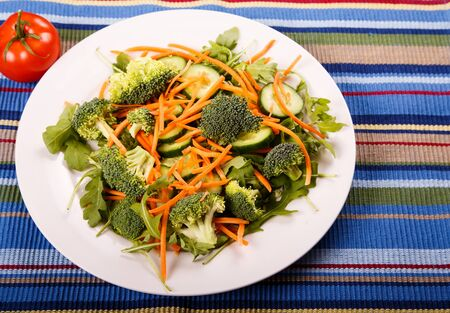 A healthy salad of arugula, spinach, cucumbers, carrots and broccoli on a whilte plate and colorful placemat.