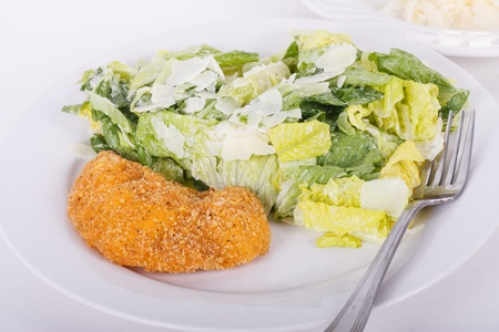 A breaded and fried chicken breast on a plate with a fresh caesar salad and fork