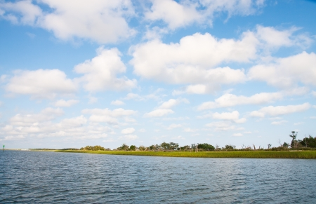 clouds in sky: A coastal salt water marsh under nice skies with puffy clouds Stock Photo