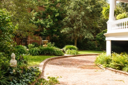 property development: Nice brick driveway curving between white home and a landscaped garden Stock Photo