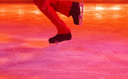 An ice skater performing under colored lights in red pants